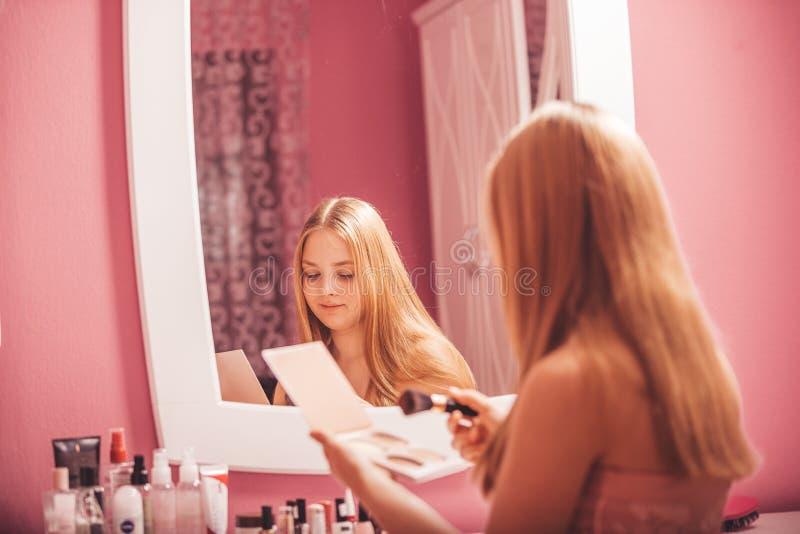 Adolescente dans une robe appliquant le maquillage sur le visage à la maison photos stock