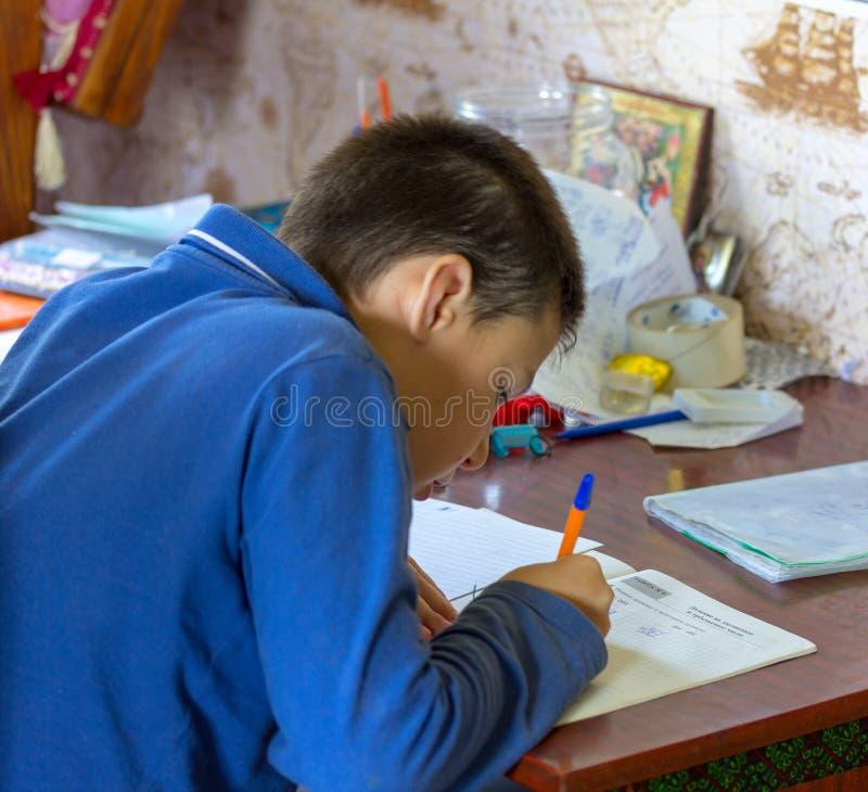 Adolescente de 11 años del muchacho que hace la preparación de la escuela foto de archivo