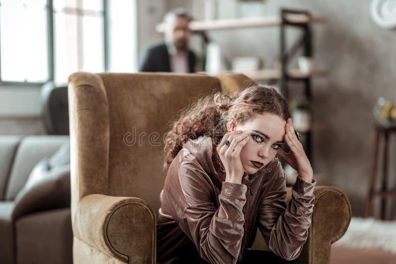 Adolescente de cabelo escuro com o cabelo encaracolado que tem a composição escura foto de stock royalty free