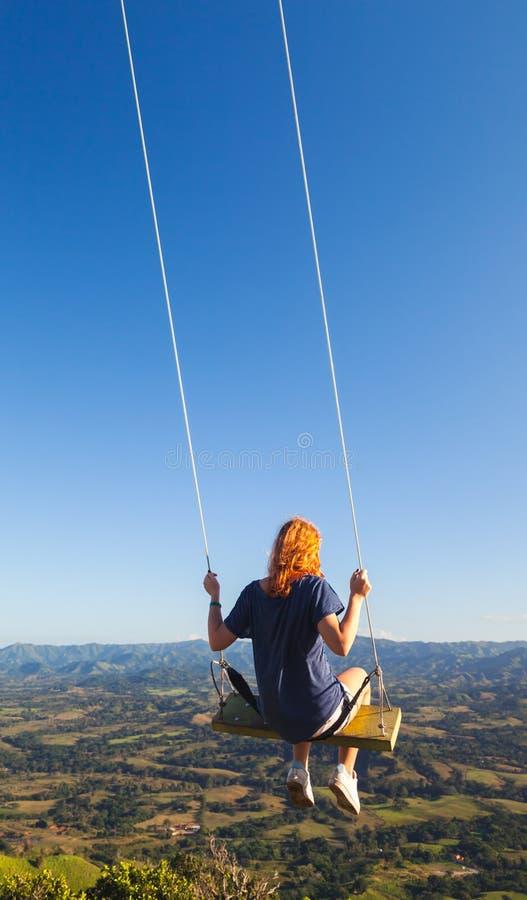 Adolescente de cabelo vermelho que balança em um balanço imagens de stock royalty free