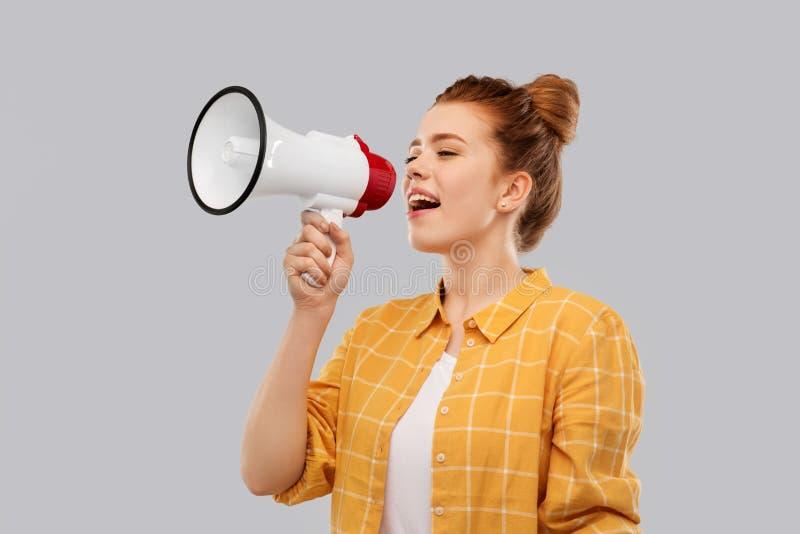 Adolescente de cabelo vermelho que fala ao megafone imagem de stock royalty free
