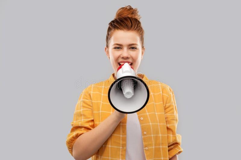 Adolescente de cabelo vermelho que fala ao megafone imagens de stock