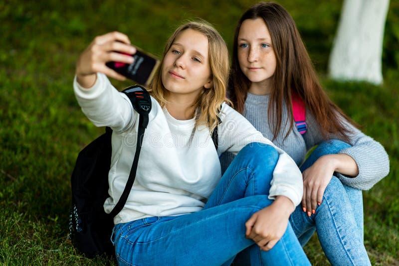 Adolescente de dos colegialas que se sienta en hierba en verano en parque En sus controles de las manos un smartphone, toma imáge imagen de archivo