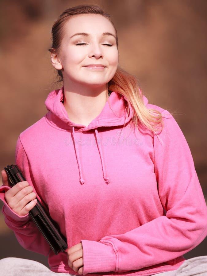Adolescente de femme dans le rose avec le comprimé obtenant un certain soleil extérieur images stock