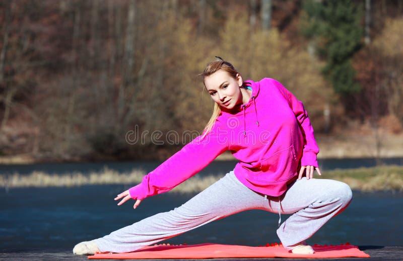 Adolescente de femme dans le survêtement faisant l'exercice sur le pilier extérieur image stock