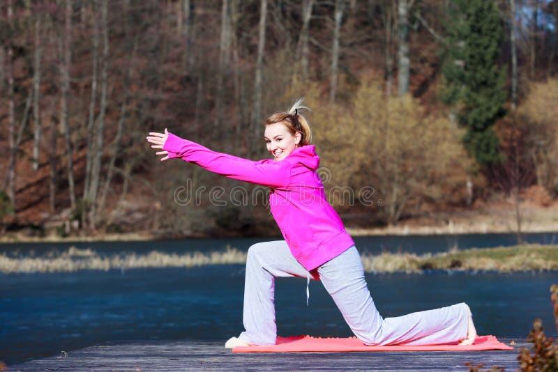 Adolescente de femme dans le survêtement faisant l'exercice sur le pilier extérieur photos stock