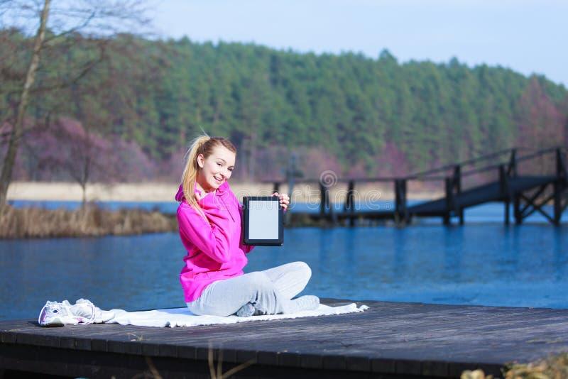Adolescente de femme dans le survêtement montrant le comprimé sur le pilier extérieur image libre de droits