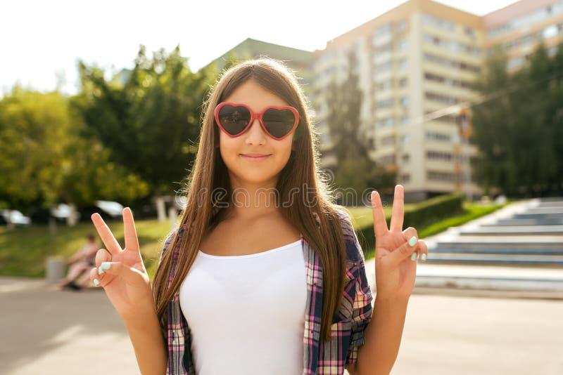 Adolescente de fille 9-13 années, se tenant en été en parc de ville, victoire de geste de main bonjour Pendant l'été, sourires he photos stock