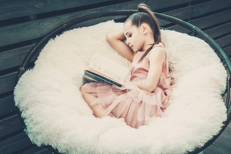 Adolescente de fille dans une robe rose se reposant dans une chaise sur un plaid blanc de fourrure et lisant un livre photographie stock libre de droits