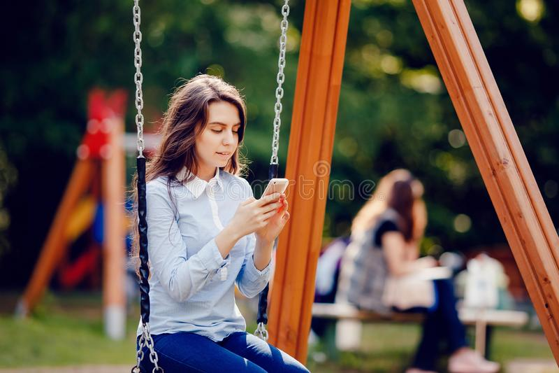 Adolescente de la estudiante que balancea en un oscilación y que usa el teléfono para las miradas de la comunicación en marco imágenes de archivo libres de regalías