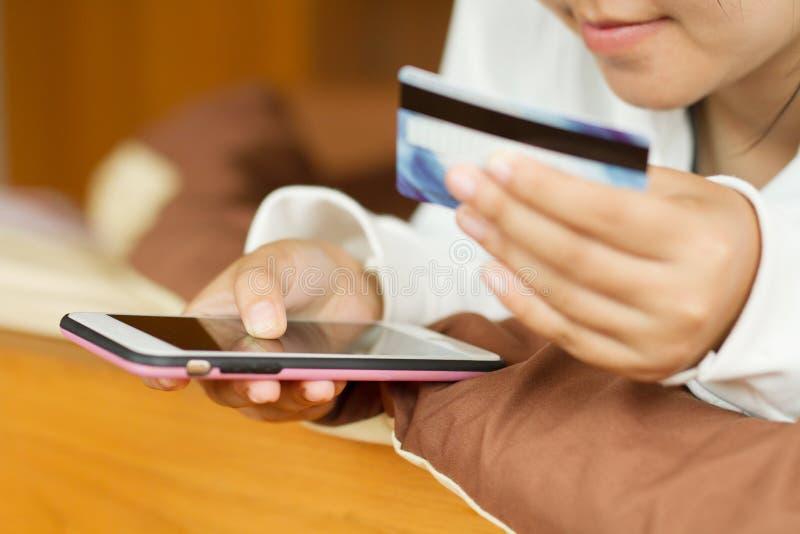 Adolescente de la mujer que sostiene el teléfono elegante con la tarjeta de crédito mientras que hace compras en Internet en casa foto de archivo