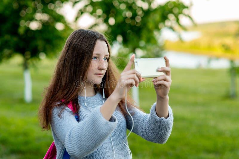 Adolescente de la niña en parque del verano al aire libre en las manos que sostienen smartphone que escucha la música y que toma  foto de archivo