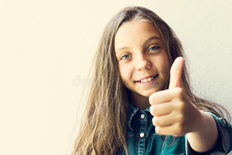 Adolescente de olhos azuis, louro bonito da menina, em uma camisa da sarja de Nimes, com um polegar acima Em um fundo claro Copie fotografia de stock royalty free