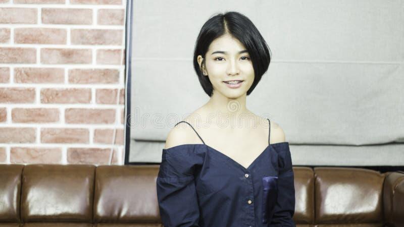 Adolescente de portrait dans la robe bleue luxueuse, souriant heureusement avec un regard lumineux, se reposant sur un sofa en cu photos stock