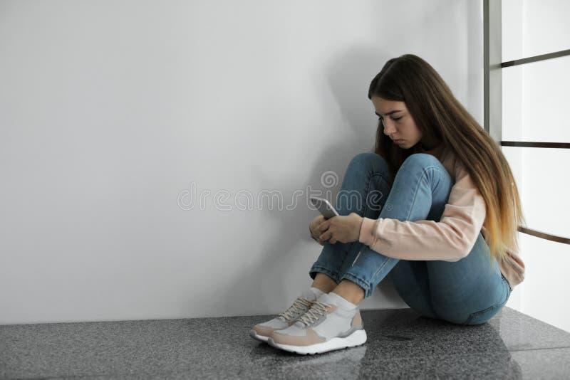 Adolescente de renversement avec le smartphone se reposant sur le plancher près du mur photo libre de droits