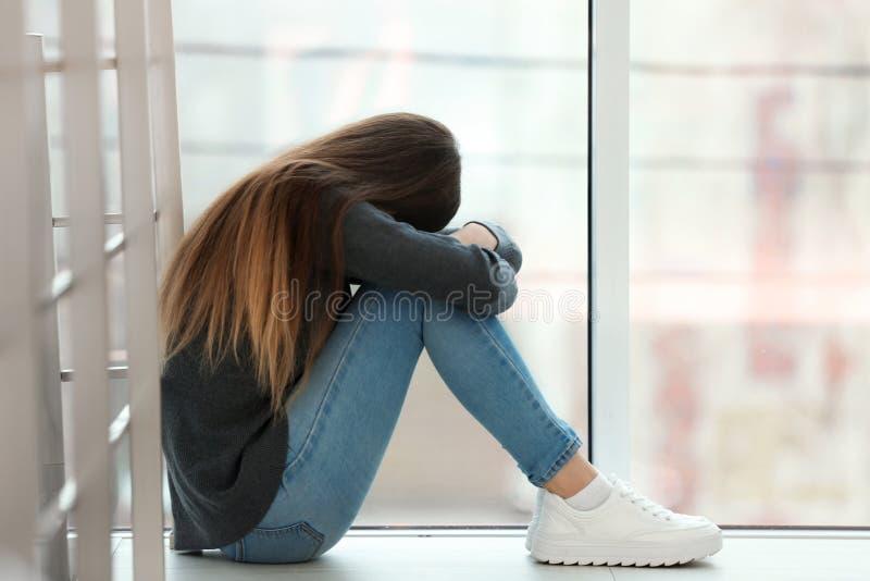Adolescente de renversement s'asseyant ? la fen?tre L'espace pour le texte images libres de droits