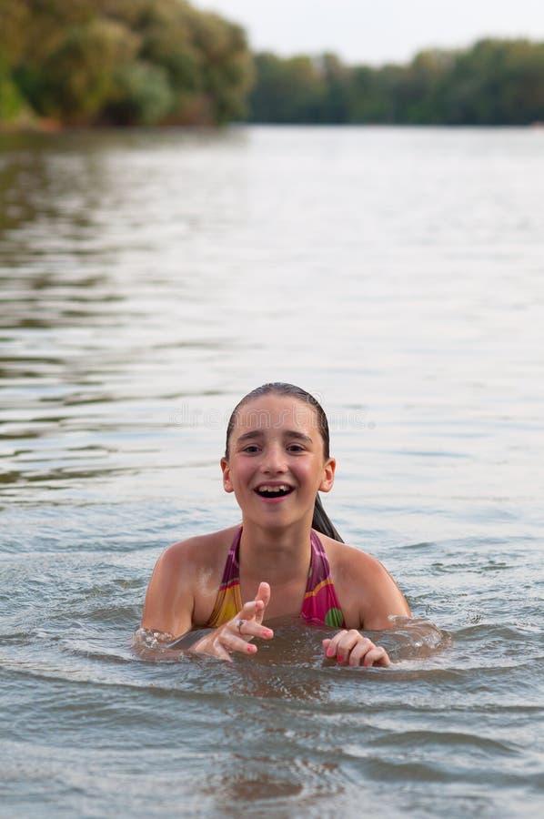 Adolescente de sorriso bonito que tem o divertimento no rio imagem de stock