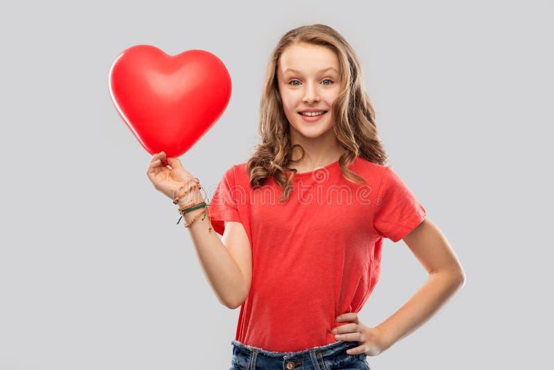 Adolescente de sorriso com coração vermelho o balão dado forma imagem de stock royalty free