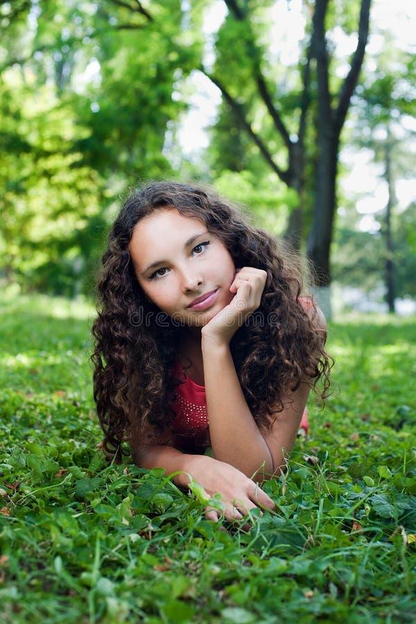 Adolescente de sorriso com o cabelo encaracolado que encontra-se em uma grama verde imagens de stock royalty free