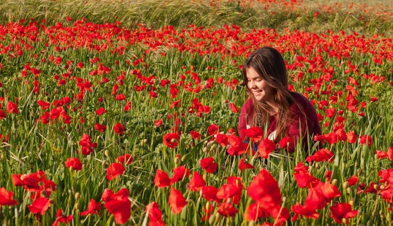 Adolescente de sorriso feliz que senta-se em um campo vermelho da papoila imagem de stock