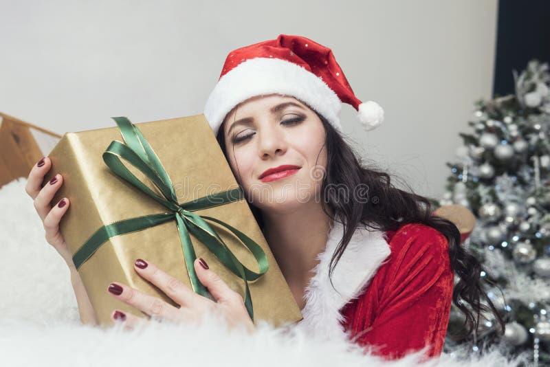 Adolescente de sorriso no chapéu do ajudante de Santa com muitas caixas de presente no fundo branco Menina emocional positiva de  fotos de stock