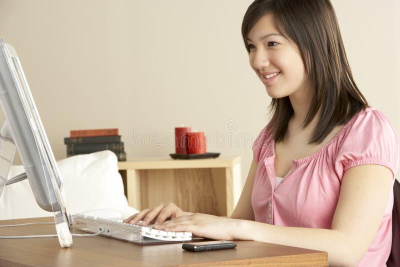 Adolescente de sorriso no computador em casa imagens de stock