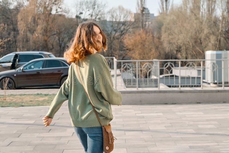 Adolescente de sorriso novo de passeio da menina que olha in camera através da parte traseira com cabelo vermelho marrom na camis fotos de stock royalty free