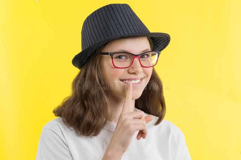 Adolescente de sorriso positivo 13 14 anos velho com vidros, um chapéu mostra um sinal do silêncio, guarda um dedo em seus bordos imagem de stock