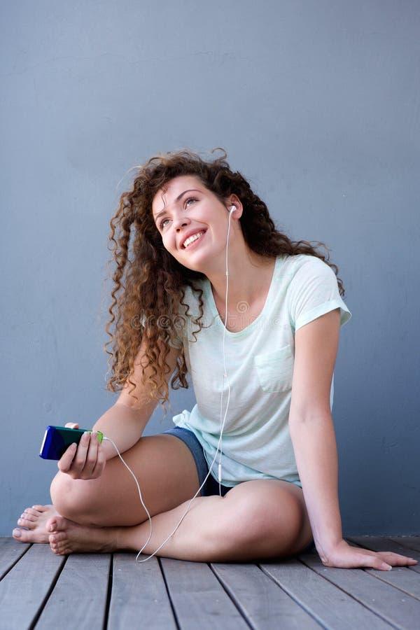Adolescente de sorriso que escuta a música que senta-se no assoalho fotografia de stock royalty free