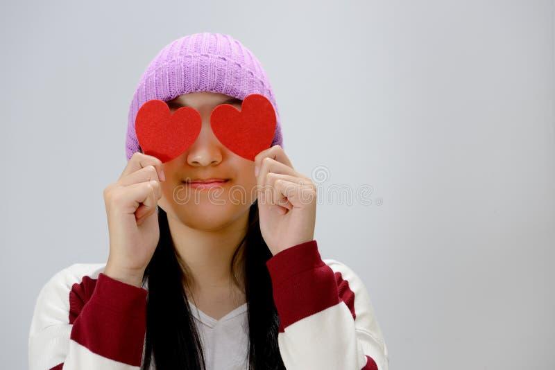 Adolescente de sorriso que guarda corações de papel vermelhos sobre o fundo cinzento fotos de stock royalty free