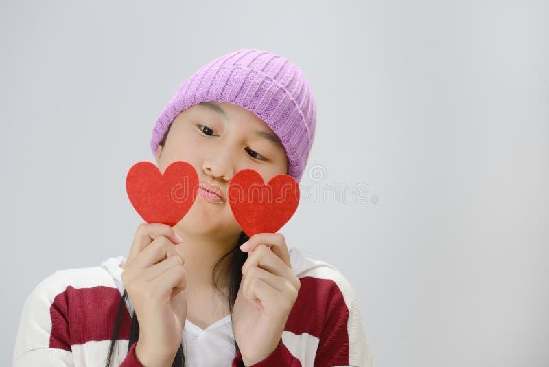 Adolescente de sorriso que guarda corações de papel vermelhos sobre o fundo cinzento imagem de stock