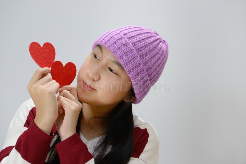 Adolescente de sorriso que guarda corações de papel vermelhos sobre o fundo cinzento fotografia de stock royalty free