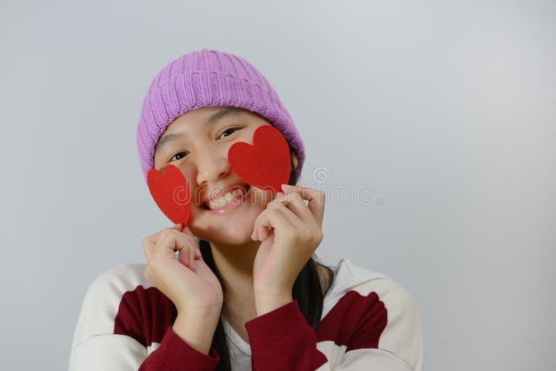Adolescente de sorriso que guarda corações de papel vermelhos sobre o fundo cinzento imagens de stock royalty free