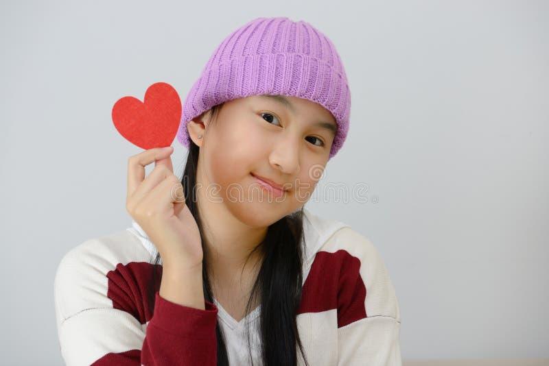 Adolescente de sorriso que guarda corações de papel vermelhos sobre o fundo cinzento imagens de stock