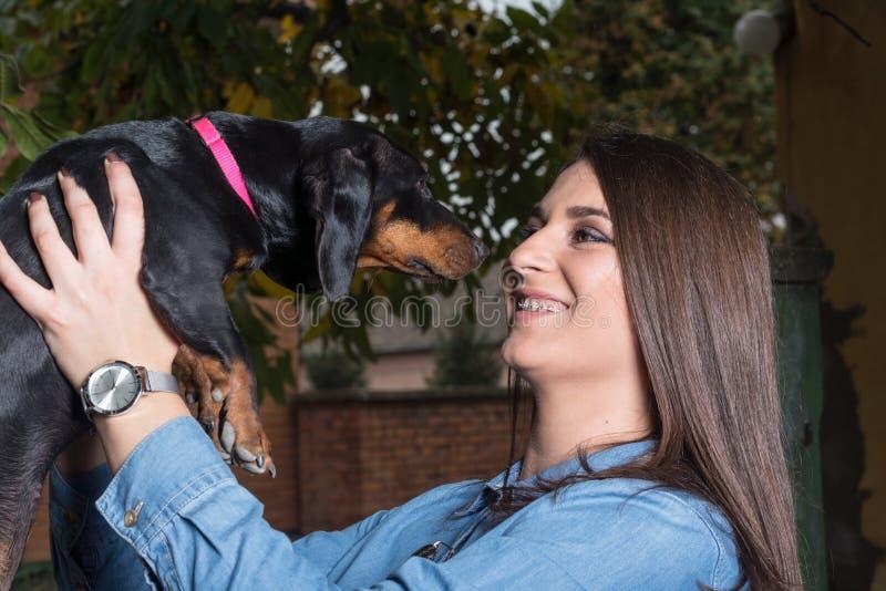 Adolescente de sorriso que guarda o cão preto do bassê na mão imagem de stock royalty free