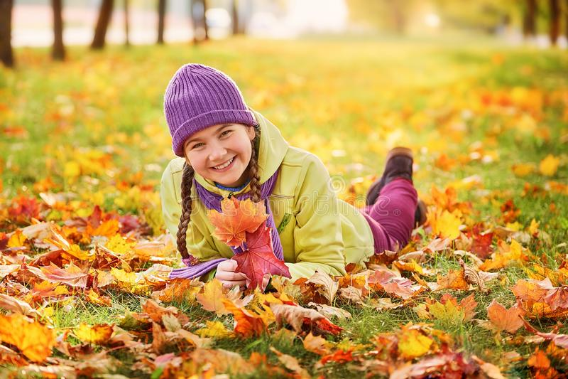 Adolescente de sorriso que relaxa no amarelo do parque do outono amarelo retrato do outono do bebê na folha de bordo fotos de stock