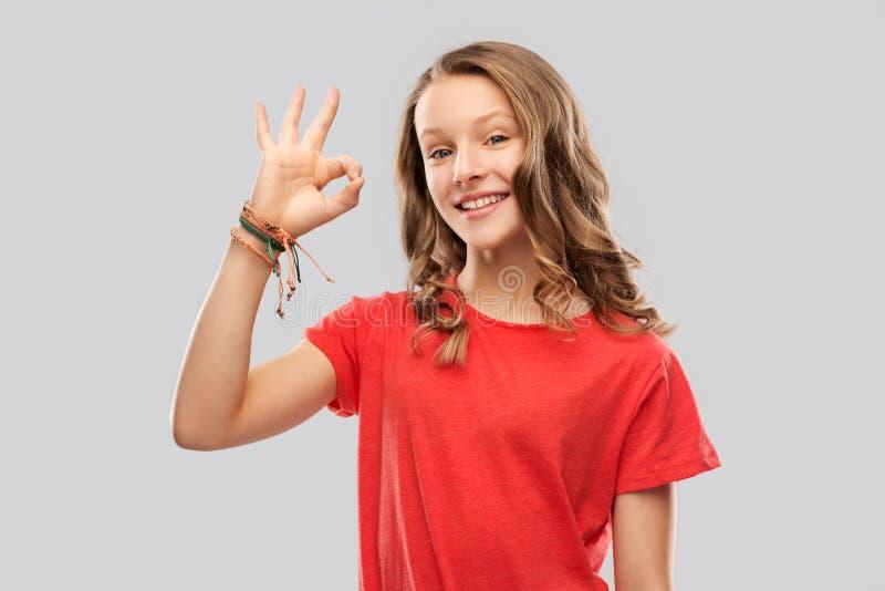 Adolescente de sourire dans l'ok rouge d'apparence de T-shirt image stock