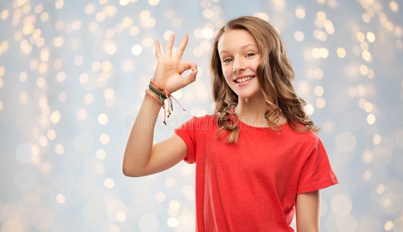 Adolescente de sourire dans l'ok rouge d'apparence de T-shirt photo libre de droits