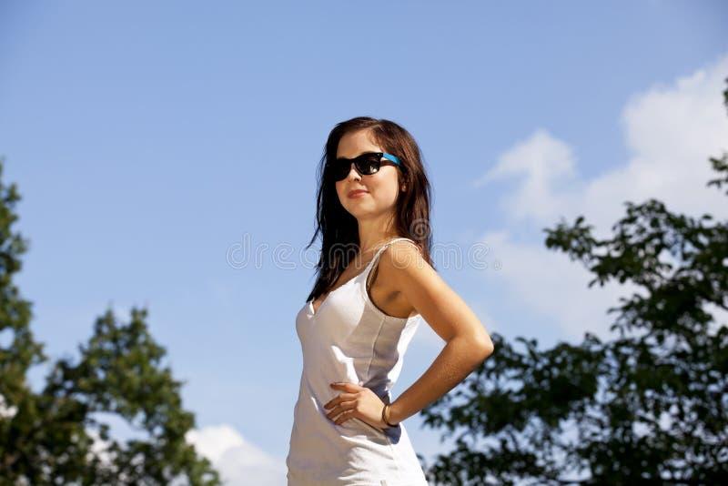 Adolescente de sourire de brunette avec des lunettes de soleil photo libre de droits