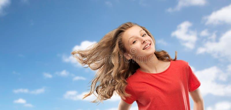 Adolescente de sourire en rouge avec de longs cheveux onduleux photographie stock libre de droits