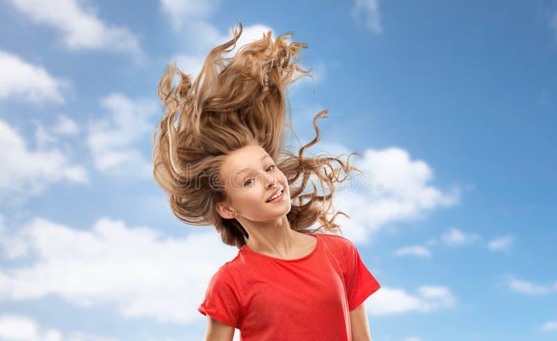Adolescente de sourire en rouge avec de longs cheveux onduleux photo libre de droits