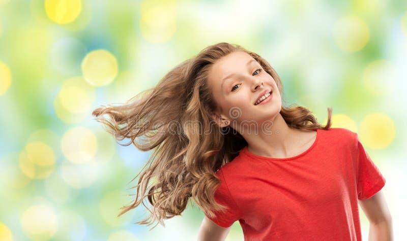 Adolescente de sourire en rouge avec de longs cheveux onduleux image stock