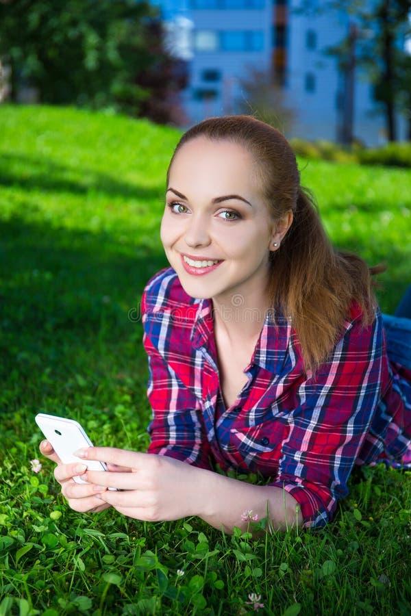 Adolescente de sourire se trouvant avec le téléphone intelligent sur l'herbe en parc photo stock