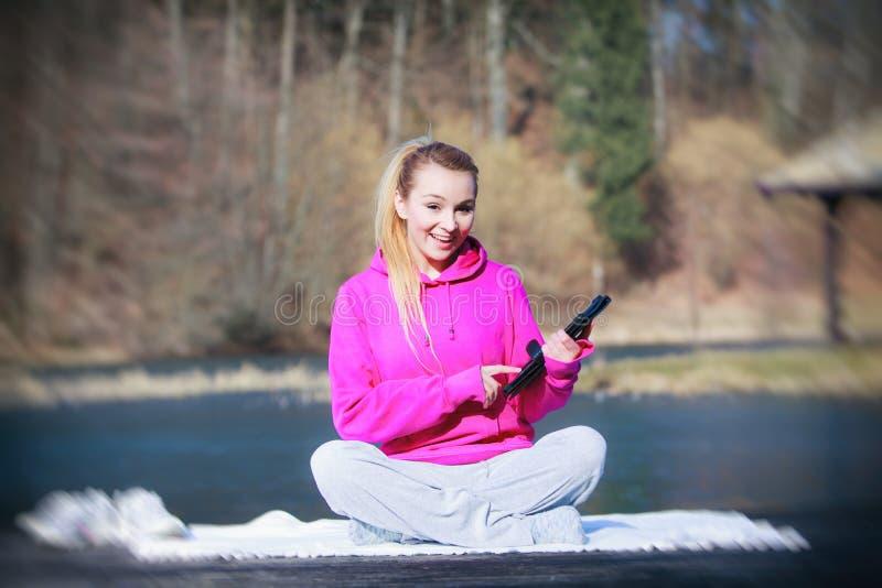 Adolescente de sport employant le touchpad de comprimé sur le pilier photos stock