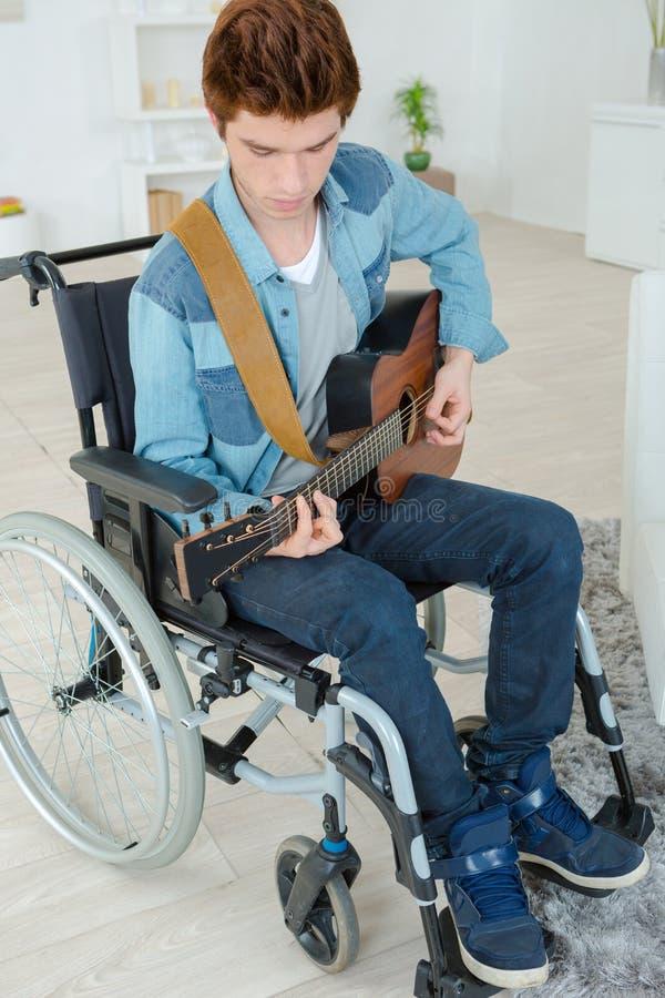 Adolescente deficiente que joga a guitarra fotografia de stock royalty free