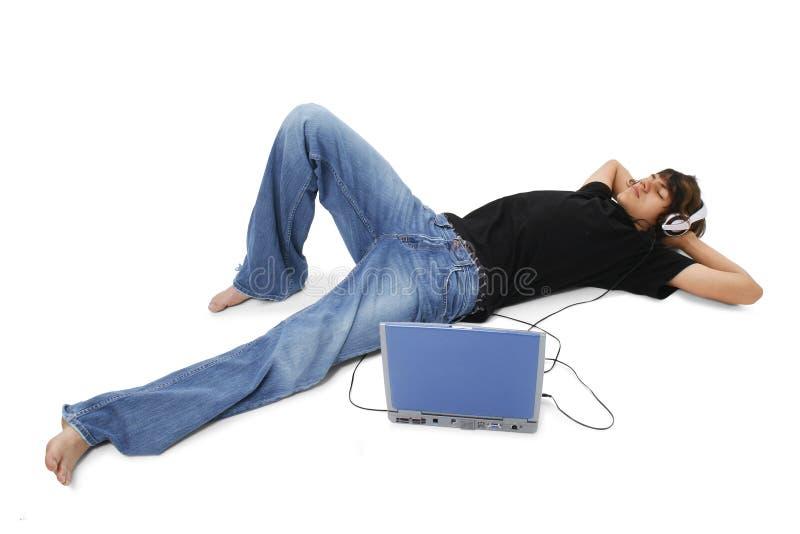 Adolescente del muchacho que pone en el suelo que escucha los auriculares fotos de archivo libres de regalías
