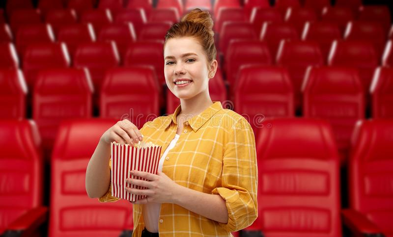 Adolescente del pelirrojo con palomitas en el cine fotos de archivo
