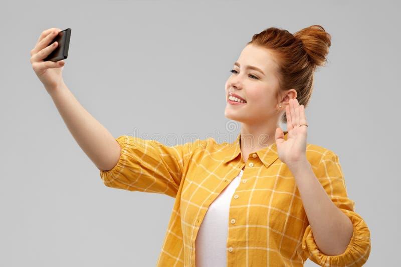 Adolescente del pelirrojo que toma el selfie por smartphone fotografía de archivo