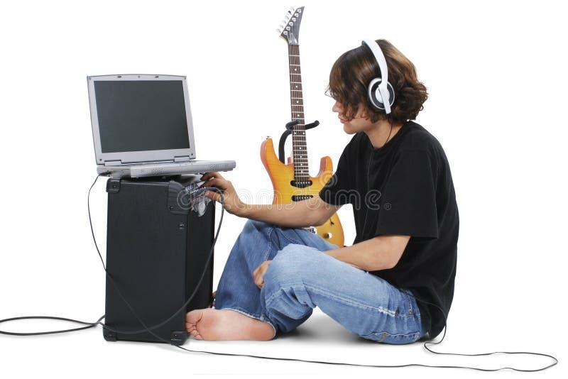 Adolescente del ragazzo con la chitarra elettrica ampère ed il computer portatile fotografie stock