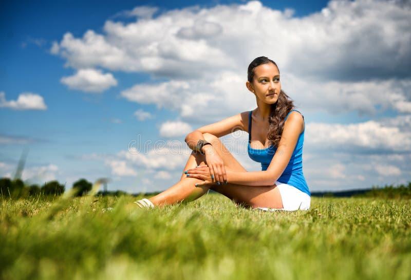 Adolescente delgado bronzeado em um campo verde imagem de stock
